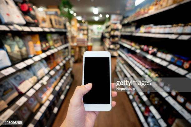 unrecognizable person holding a smartphone using an application while standing between aisles at supermarket - market retail space stock photos and pictures