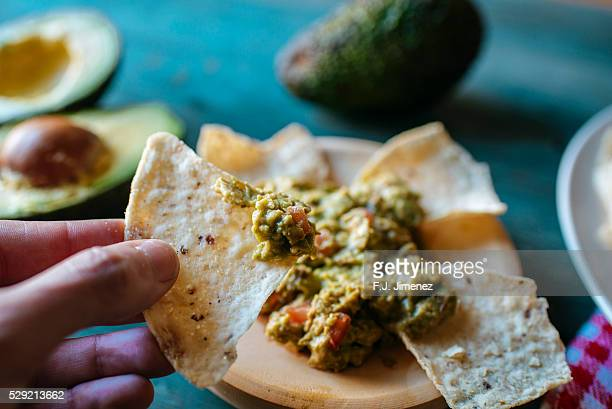 unrecognizable person holding nachos with guacamole - appetiser stock photos and pictures