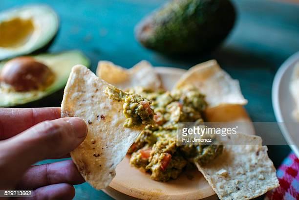 Unrecognizable person holding nachos with guacamole