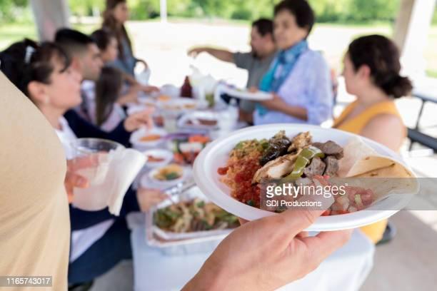 認識できない人がメキシコ料理の皿を持っている - ポットラック ストックフォトと画像