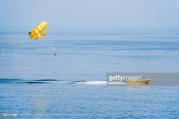 Unrecognizable person parasailing over sea, Albufeira, Algarve, Portugal