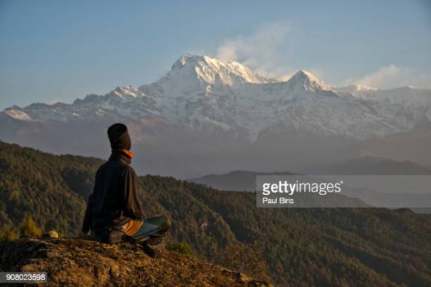 Unrecognizable person practicing yoga at sunrise looking to  the Annapurna, Nepal