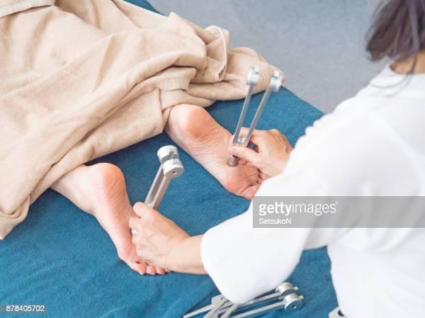 Unrecognizable person recieving tuning fork therapy