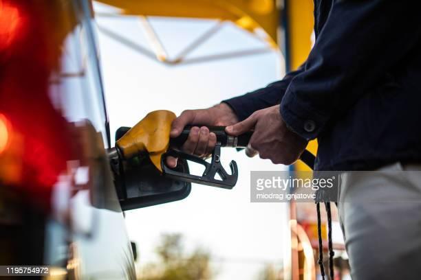 pessoa irreconhecível reabastecendo gás em um tanque de gasolina - estação - fotografias e filmes do acervo