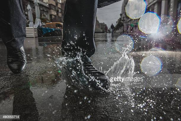 unrecognizable person stepping into a puddle during rainy day. - puddle stock pictures, royalty-free photos & images