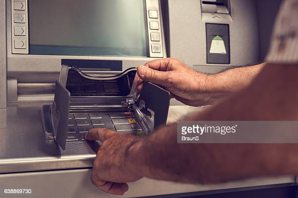 Unrecognizable person typing PIN on a cash machine.