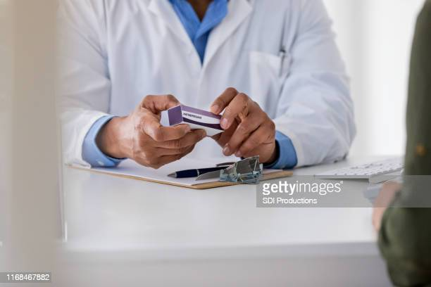 unrecognizable pharmacist holds generic drug while talking to customer - generic drug stock pictures, royalty-free photos & images