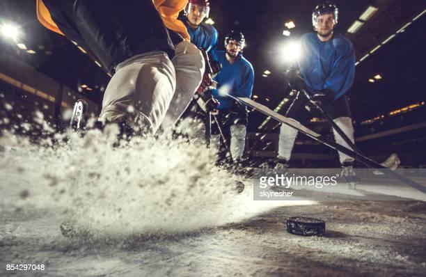 Unrecognizable player splashing ice during hockey match.