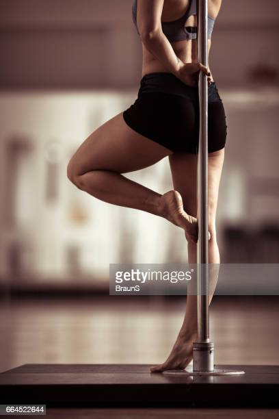 Unrecognizable pole dancer's body leaning on a pole.