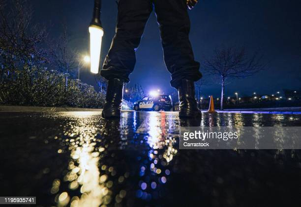 unrecognizable police officers in rainy night police control. - arrest stock pictures, royalty-free photos & images