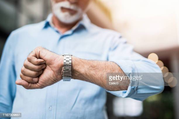 onherkenbaar senior man controletijd op een luxe horloge. - polshorloge stockfoto's en -beelden
