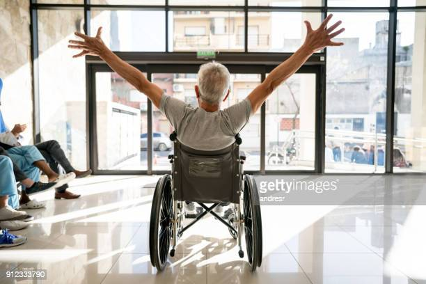 Unrecognizable senior patient leaving the clinic on a wheelchair with his arms up