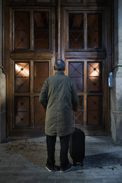 Unrecognizable  Senior retired man waiting outside a large wooden gate. Old visitor with small travel suitcase arriving to a house after a long trip