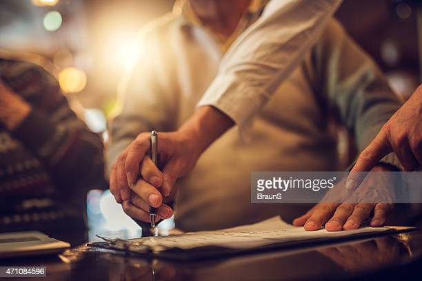 unrecognizable senior signing a contract with help of financial advisor. - human body part stock pictures, royalty-free photos & images