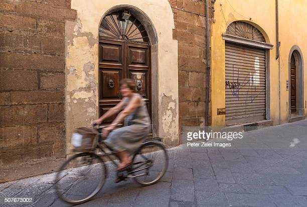 Unrecognizable senior woman cycling in the streets of Lucca (Tuscany, Italy)