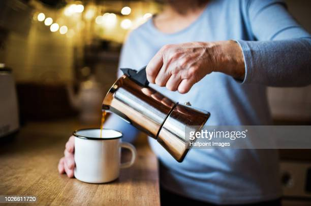 unrecognizable senior woman making coffee in the kitchen at home. - coffee maker stock pictures, royalty-free photos & images