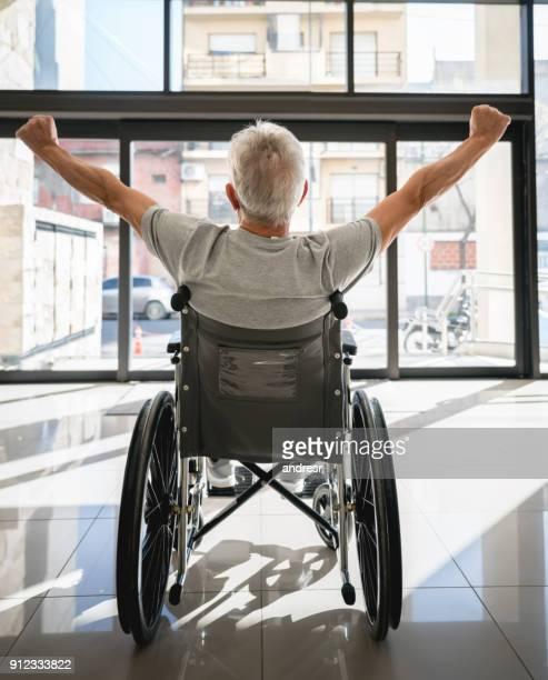車椅子で診療所を出て彼の腕で希望に満ちた感じて認識できない seniro 患者