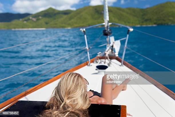irreconhecível sexy mulher tomando banho de sol em um barco à vela nas ilhas virgens - fotografia imagem - fotografias e filmes do acervo