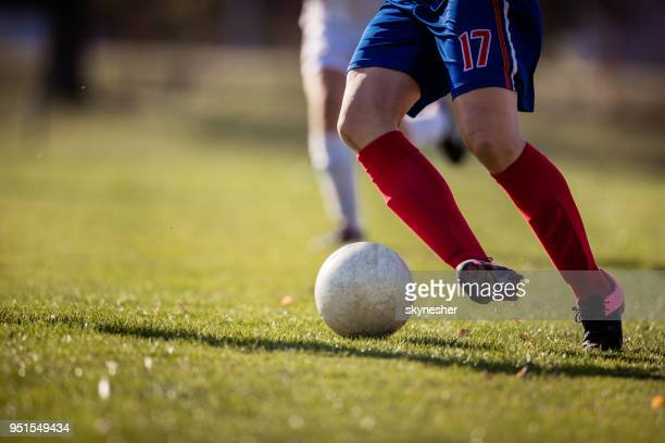 unrecognizable soccer player dribbling the ball on a match. - women's soccer stock pictures, royalty-free photos & images