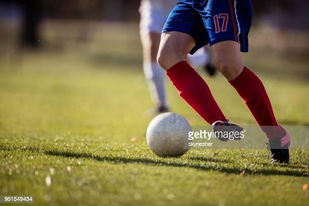 joueur de soccer méconnaissable dribble la balle sur un match. - football féminin photos et images de collection
