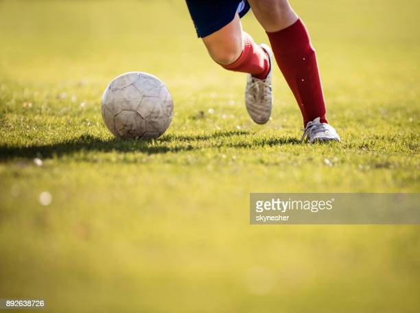 Unrecognizable soccer player running with a ball.