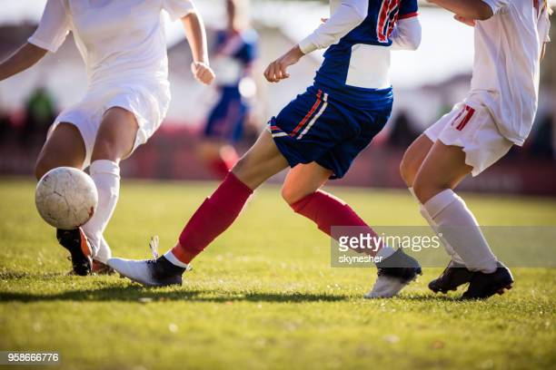 unrecognizable soccer player running with ball on a match while avoiding her opponent. - tackling stock pictures, royalty-free photos & images
