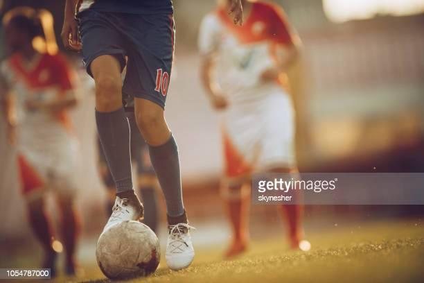 oigenkännlig fotbollsspelare med en boll på en match. - anfallsspelare fotboll bildbanksfoton och bilder