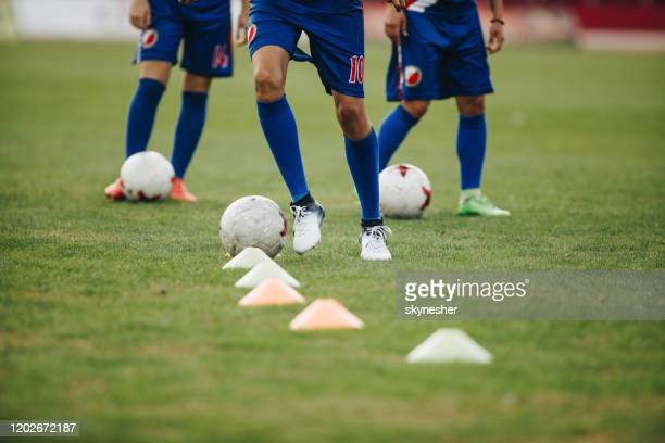 unrecognizable soccer players exercising dribbling among cones on a sports training. - cleats stock pictures, royalty-free photos & images
