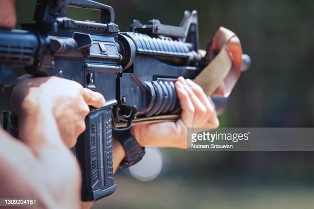 unrecognizable soldier holding machine gun - machine gun stock pictures, royalty-free photos & images