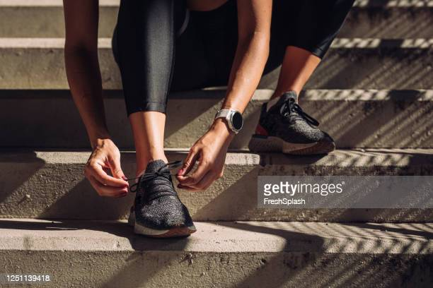 unrecognizable sportswoman tying laces on running sneakers, a close up - black shoe stock pictures, royalty-free photos & images