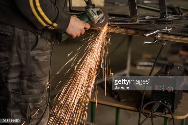 Irreconocible trabajador acero pulido metal con la sierra en un taller.