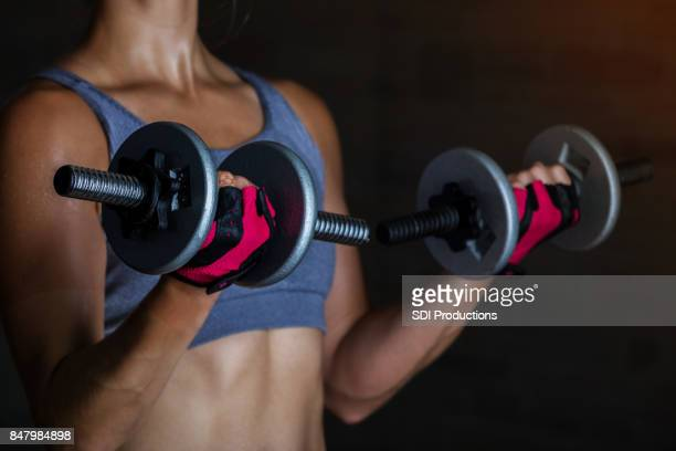 Unrecognizable strong young woman during intense workout