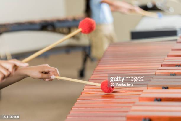 Unrecognizable student playing marimba during band practice
