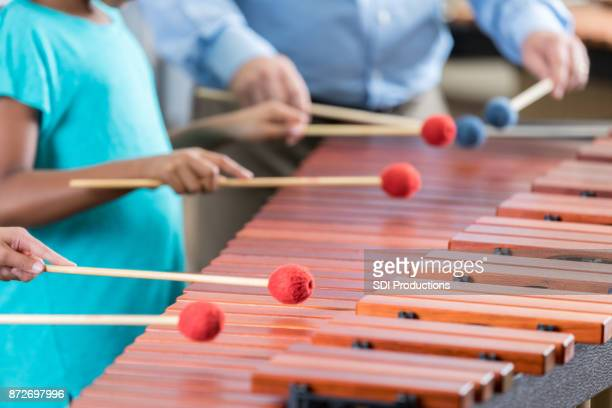 Unrecognizable students and teacher play the xylophone together