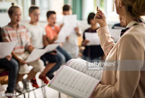 Unrecognizable teacher giving a lesson during music class.