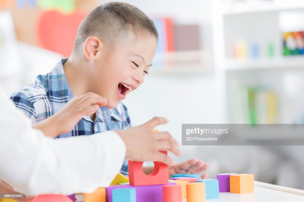 Unrecognizable teacher helps young boy with blocks : Stock Photo