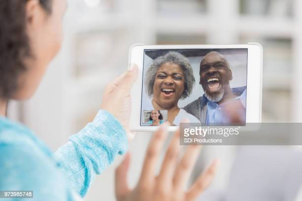 unrecognizable teenage girl has videoconference with grandparents - long distance relationship stock pictures, royalty-free photos & images