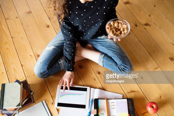nicht erkennbare teenager-mädchen mit tablet-pc auf dem boden sitzend, müsli zu essen, studieren - food journal stock-fotos und bilder