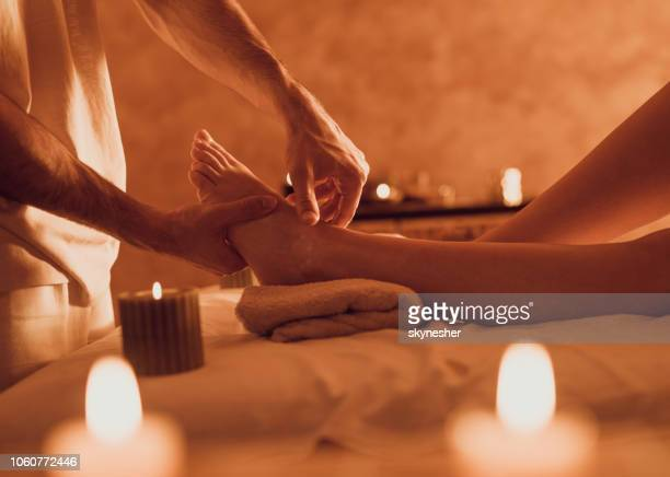 unrecognizable therapist massaging customer's foot at health spa. - foot massage stock pictures, royalty-free photos & images