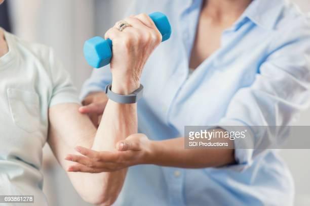 Nicht erkennbare verwendet blaue Hand Gewicht während physikalische Therapie-Sitzung