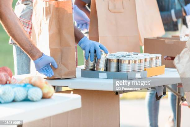 unrecognizable volunteers wear protective gloves to sort food - giving tuesday stock pictures, royalty-free photos & images