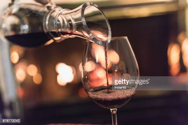 Unrecognizable woman, a decanter in her hands, pouring red wine in a glass.