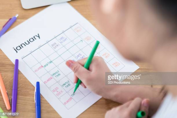 unrecognizable woman adds items to full calendar - january stock pictures, royalty-free photos & images
