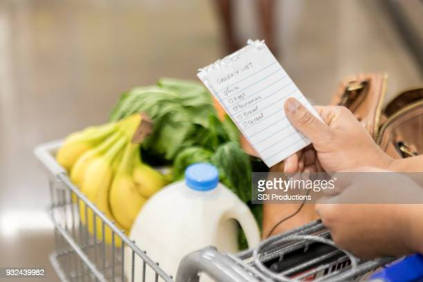 unrecognizable woman checks items off grocery list - list stock pictures, royalty-free photos & images