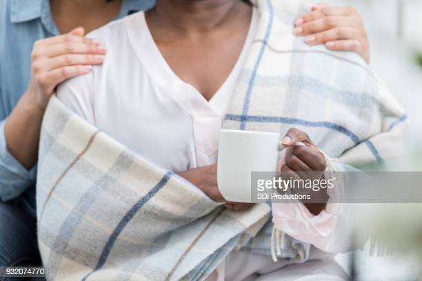 Unrecognizable woman comforts her ill friend