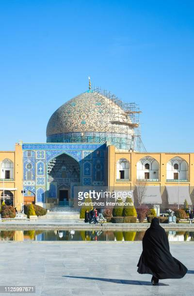 unrecognizable woman dressed in a religious hijab walking on 'emam square' ('naqsh-e jahan square') towards sheikh lotfollah mosque ('masjed-e sheikh lotfollah') in isfahan, iran - burka stock pictures, royalty-free photos & images