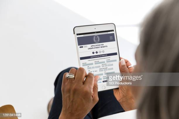 unrecognizable woman files for unemployment benefits - form filling stock pictures, royalty-free photos & images
