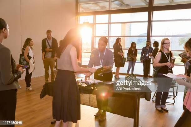 unrecognizable woman gets information at expo registration table - town hall stock pictures, royalty-free photos & images
