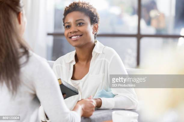 unrecognizable woman gives her friend a bible - american influence stock photos and pictures