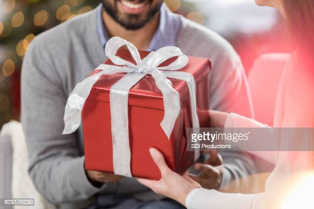 Unrecognizable woman gives husband a Christmas present